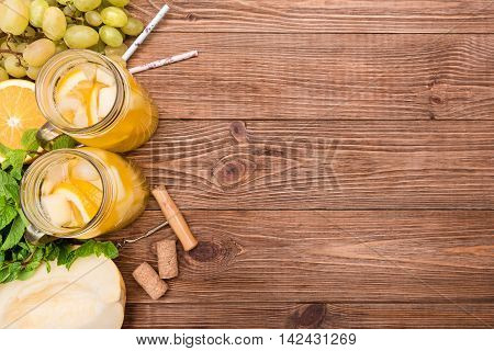 Homemade white wine sangria with melon and orange on a wooden table.