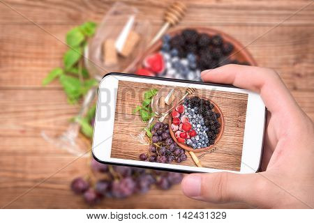 Hands taking photo red wine sangria with fresh berries with smartphone.