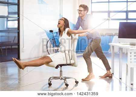 Business executive pushing businesswoman in office chair at workplace