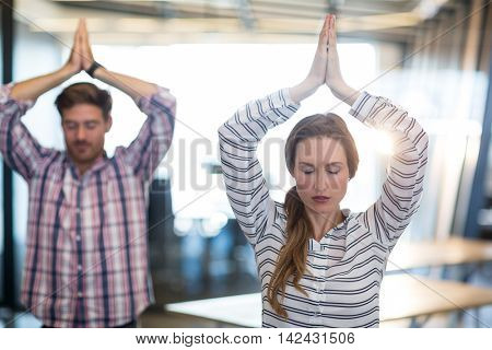 Business people performing yoga in office