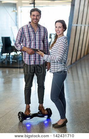 Portrait of man on hoverboard using digital tablet with colleagues in office