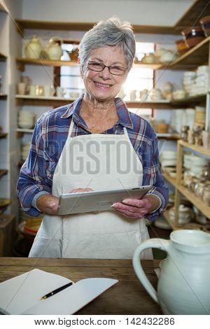 Happy female potter using digital tablet in pottery workshop