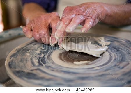 Close-up of potter removing clay from pottery wheel in pottery workshop