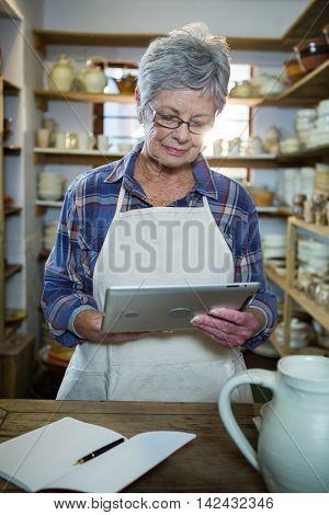 Attentive female potter using digital tablet in pottery workshop