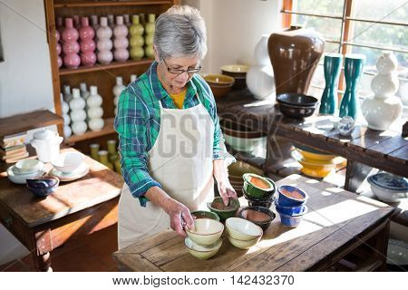 Female potter arranging bowl on worktop in pottery workshop
