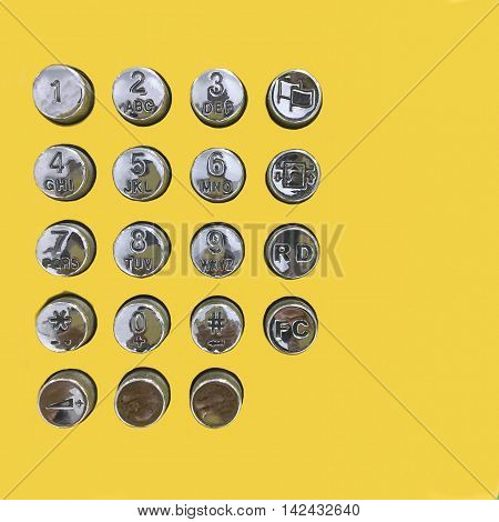 Dial number button of public telephone on yellow background.
