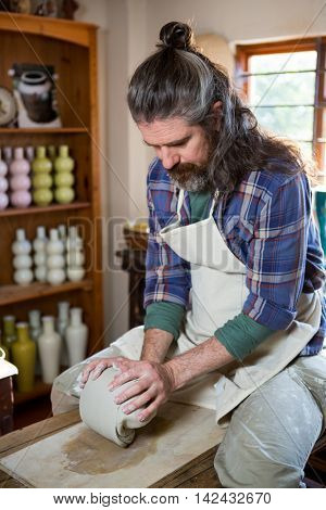 Male potter molding clay in pottery workshop