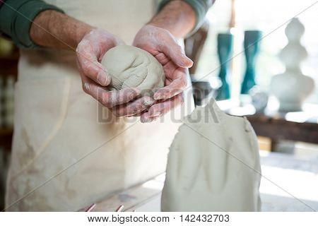 Mid section of male potter molding clay in pottery workshop