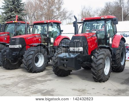 Moldova Chisinau, 05 may 2016: New red powerfull tractors at exhibition of agricultural machinery