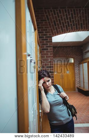 Stressed mature student standing in locker room at college