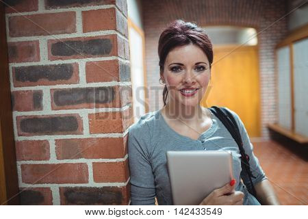 Portrait of mature student holding digital tablet in the locker room at college