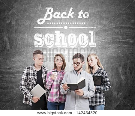 College students standing near chalkboard with words back to school written on it holding coffee netbook daily calendar and tablet. Concept of new school year