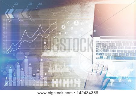 Trader working on laptop with charts and graphs in foreground. Concept of stock market. Elements of this image furnished by NASA. Toned image. Double exposure