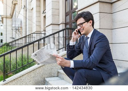 Side view of attractive smiling businessman sitting outside on concrete stairs reading newspaper and talking on phone