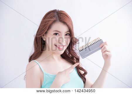 Beautiful young woman with health teeth and hold teeth whitening tool. Isolated over white background asian beauty