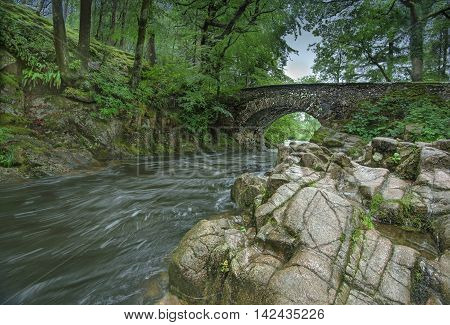 The River Esk speeding under an old stone bridge at Dalegarth in the Lake District National Park, Cumbria England