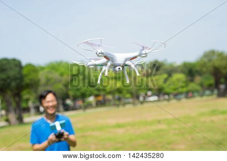 man play drone in the park happily asian