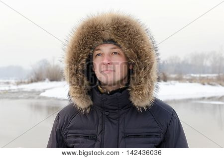 Portrait of a man in a fur hood on a winter background.