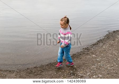 Girl walking on the river bank. She is wearing a sweater and jeans. She is looking like she is dancing and singing os saying something.