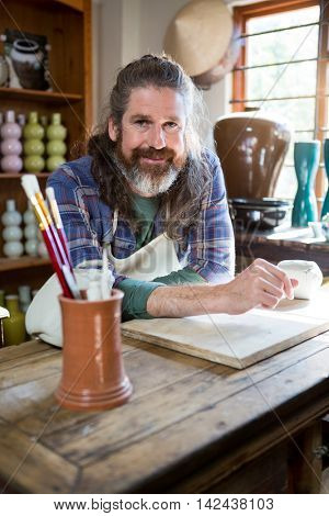 Portrait of male potter leaning on table in pottery workshop