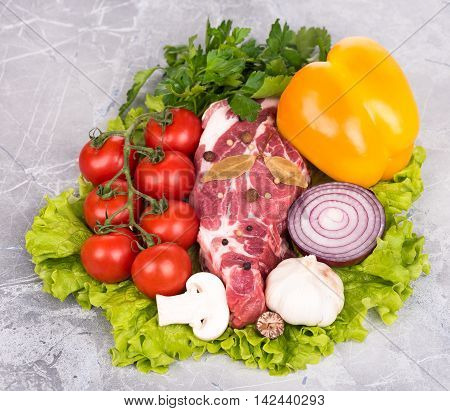Raw pork with spices and vegetables over the table-top background