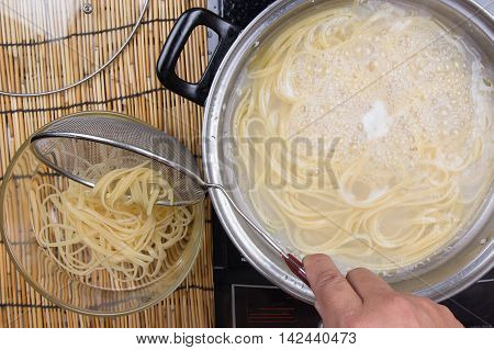 Spaghetti lifted on of cold water with colander / cooking spaghetti concept