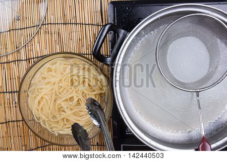 Spaghetti lifted on of cold water with tongs / cooking spaghetti concept
