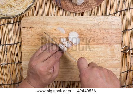slicing red onion on wooden broad / cooking spaghetti concept