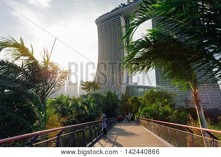 SINGAPORE SINGAPORE - FEBRUARY 17: Touristis walking at the Gardens By The Bay park with Marina Bay Sands Building on the background on February 17 2016 in Singapore.