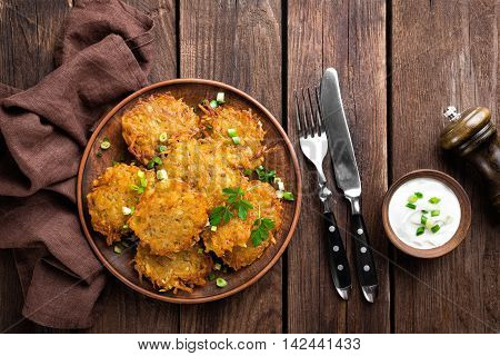 potato pancakes on plate on dark wooden table top view