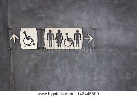 Toilet sign and direction on exposed concrete wall background