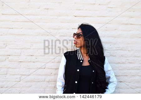 Portrait of young latin woman outdoors with sun glasses. Trendy and urban clothes.