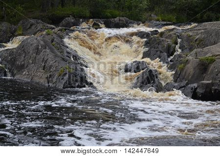 waterfall with moss-covered boulders, surrounded by greenery on the river. Tohmajoki the village Ruskeala in Russian Karelia