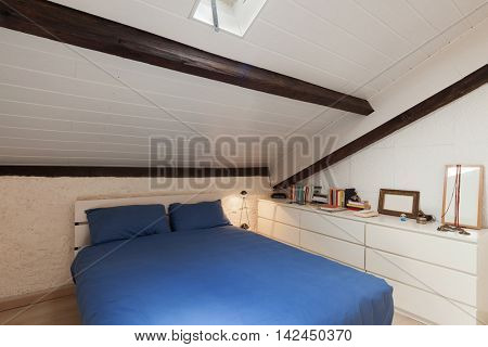 Bedroom of a loft, double bed with blue bedding