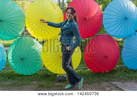 Cheerful woman on the background of multi-colored umbrellas. People