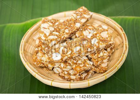 Thai sweet made of rice, nut, sesame-seeds and sugar stack on banana leaf background