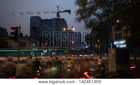 Motion shot of road traffic in night city of Hanoi, Vietnam. Motorbikes waiting at the busy crossroad