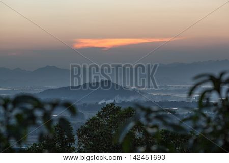 Vietnam scenery in the evening. Foggy landscape with mountains and river in the distance, trees in foreground