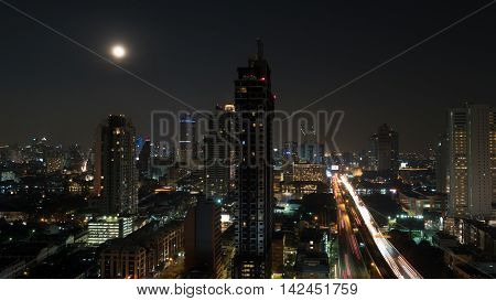 Bangkok panorama at night. View to the illuminated high-rise buildings and skyscrapers with transport traffic on highway. Capital of Thailand