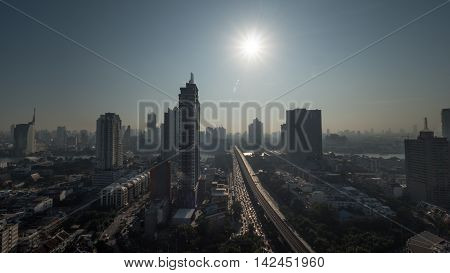 Cityscape of Bangkok, Thailand. Bright morning sun shining over the metropolis with high-rise buildings and traffic on motorway