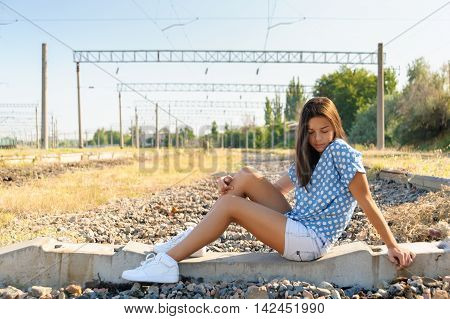 Brunette girl teenager sitting on the concrete of unfinished rail track outside the city