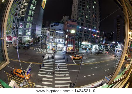 SEOUL, SOUTH KOREA - OCTOBER 22, 2015: City highway with car traffic and pedestrians on zebra crossing at night, view from the open window