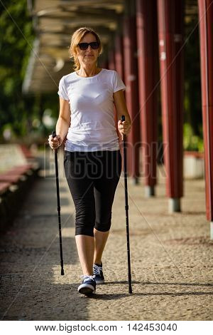 Nordic walking - middle aged woman working out in city park