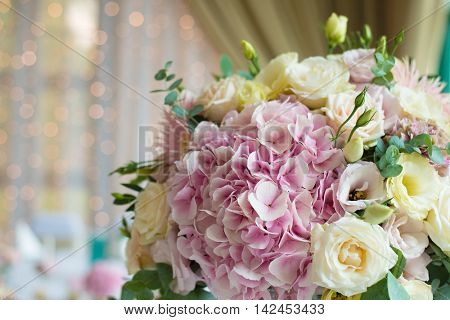 Indoors wedding reception venue with décor, selective focus on flowers