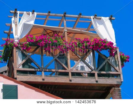 Burano Italy - May 10 2014: The original wooden veranda with table and chairs in Burano island near Venice. The island is a populat tourist site