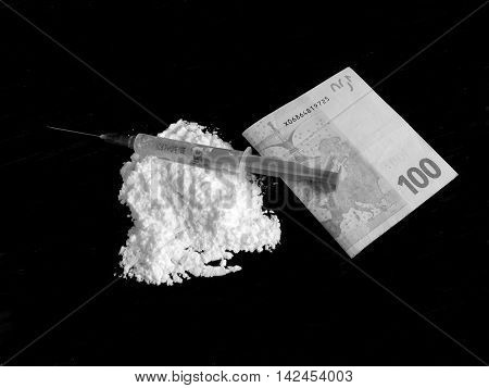 Injection on cocaine drug powder and hundred euro banknote on black background in black and white colors