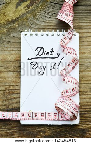 Diet concept with a notebook and red measuring tape on wooden table