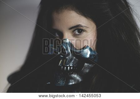 Skull mask, brunette sensual and sexy with weapons in aggressive and dangerous position