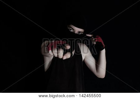 masked man pointing with finger his head in front of black background