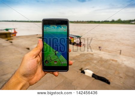 Maheshwar, India - 16th Jul 2016: Man playing pokemon go near the narmada riverbank. This popular mobile game is being played at many popular tourist places round india